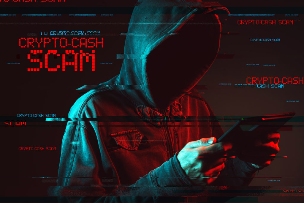 Crypto cash scam concept with faceless hooded male person using tablet computer, low key red and blue lit image and digital glitch effect