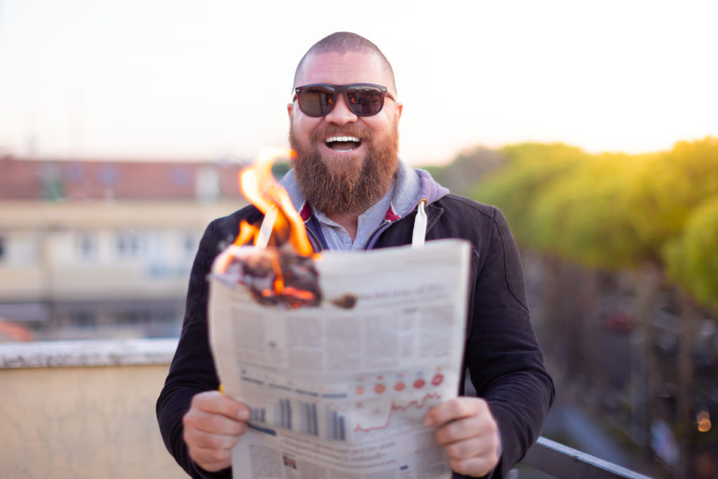 Portrait of excited (happy) bearded man looking to the newspaper (on fire) - burning magazine in man's hands - hot and breaking news concept - laughing about financial crisis