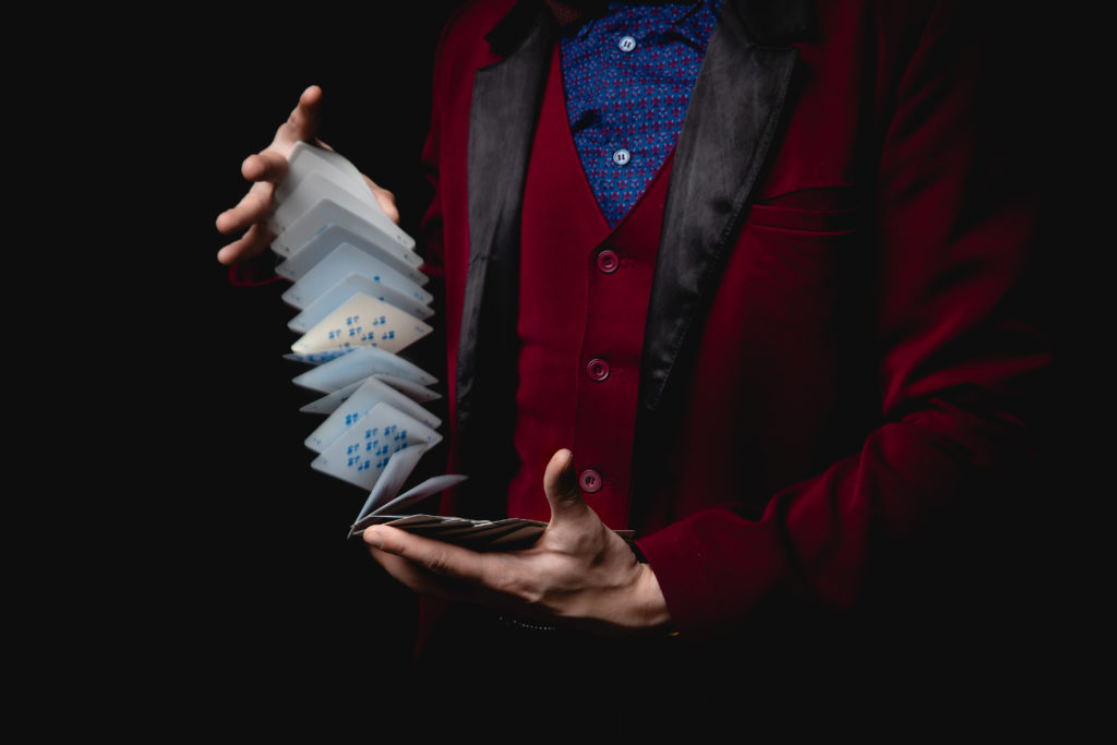 Magician shows trick with playing cards, dark background.