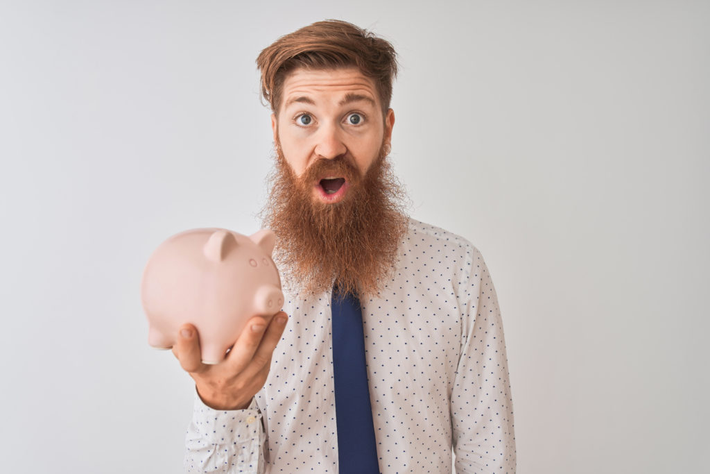 Young redhead irish businessman holding piggy bank over isolated white background scared in shock with a surprise face, afraid and excited with fear expression