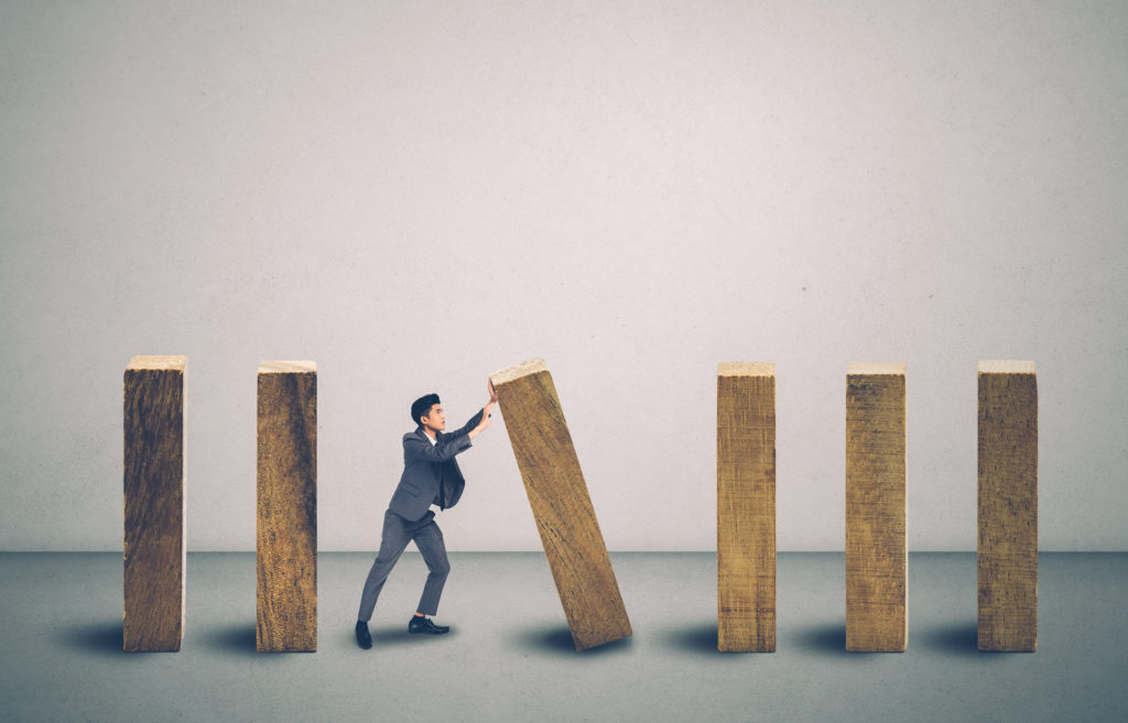 Risk of investment with economy, businessman push and stop wooden block domino with falling, management of strategy for prevention of bankruptcy, financial and insurance, crisis of business concept.