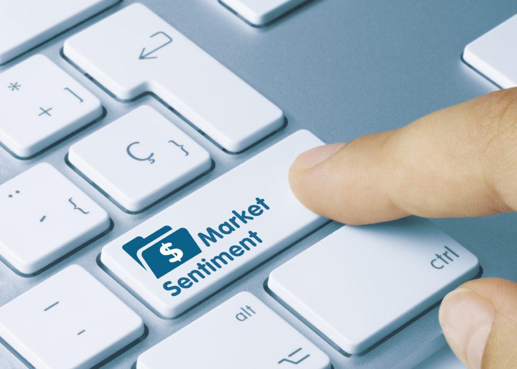 Market Sentiment Written on Blue Key of Metallic Keyboard. Finger pressing key.