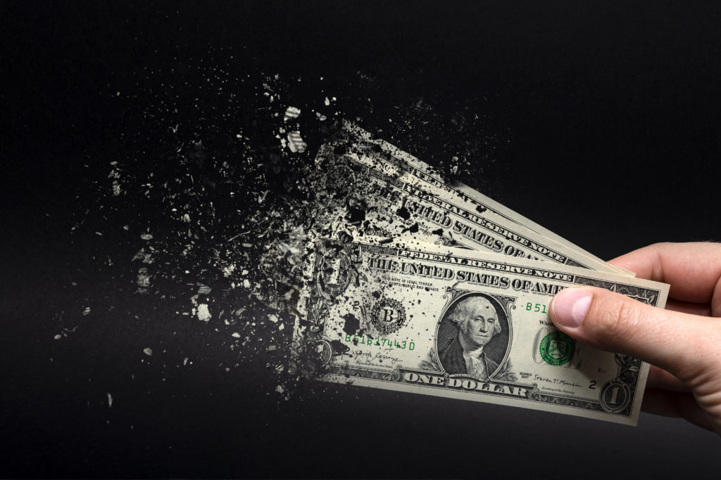 Inflation, dollar hyperinflation with black background. One dollar bill is sprayed in the hand of a man on a black background. The concept of decreasing purchasing power, inflation