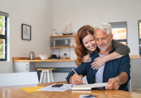 Loving mature wife embracing husband from behind while writing in book. Happy middle aged couple making to do list of purchases and discussing future plans. Cheerful senior man working at home on wooden table with beautiful woman hugging him from behind, copy space.